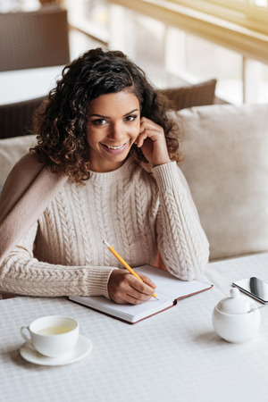 muse: Muse in everything. Delighted young inspired African American woman sitting in the cafe and being covered with a blanket while making notes in the notebook Stock Photo