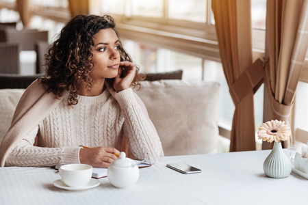 영감의 느낌. 긍정적 인 젊은 영감 아프리카 계 미국인 여자 카페에 앉아 노트를 만드는 동안 담요로 덮여있다