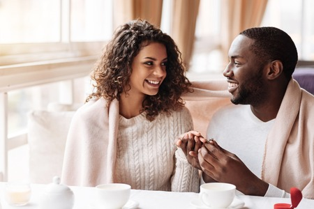 I say yes. Delighted cheerful positive African American couple sitting in the cafe and being covered with a blanket while getting engaged and expressing happiness