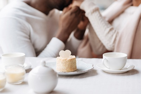 race relations: Cheerful to be next to you. Positive young happy African American couple sitting in the cafe and holding hands while expressing love and looking at each other Stock Photo