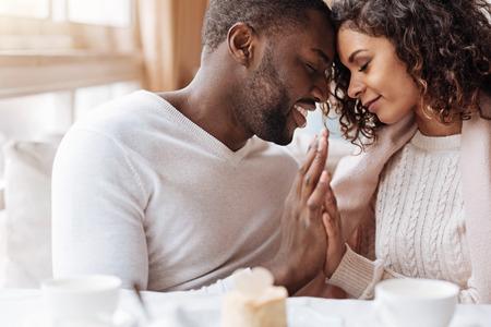 私たちの安らぎ。喜んでの平和的な肯定的なアフリカ系アメリカ人カップル、カフェに座っていると、安らぎと愛を表現しながら互いの手に触れる