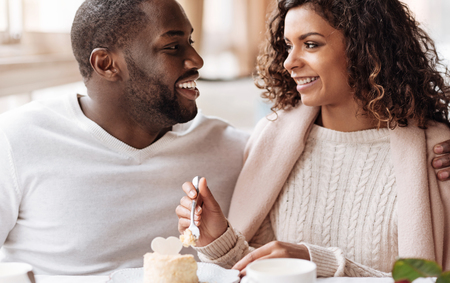 race relations: Happiness in details. Smiling positive amused African American couple sitting in the cafe and looking at each other while expressing joy and eating the cupcake