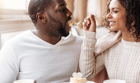 race relations: Full of care. Smiling careful playful African American couple sitting in the cafe and looking at each other while expressing joy and feeding each other with the cupcake Stock Photo