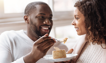 race relations: Full of romantic feelings. Cheerful careful playful African American couple sitting in the cafe and looking at each other while expressing joy and feeding each other with the cupcake