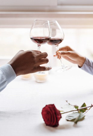 Our privacy. Positive peaceful delighted African American couple sitting in the restaurant and looking at each other while expressing affection and holding wineglasses Stock Photo