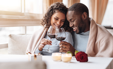 Our anniversary day. Smiling positive cheerful African American couple sitting in the restaurant and hugging each other while expressing love and drinking wine Reklamní fotografie