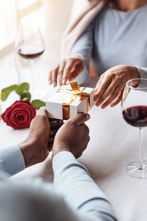 race relations: My lovely birthday present. Cheerful delighted overwhelmed African American woman sitting in the restaurant with her boyfriend while expressing happiness and getting the present in the box