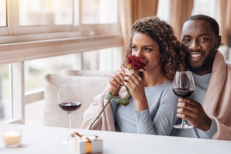 expressing: Special day. Delighted positive smiling African American couple sitting in the restaurant and hugging each other while expressing affection and drinking wine