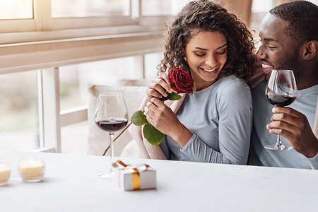 race relations: Romantic day with you . Delighted positive cheerful African American couple sitting in the restaurant and hugging each other while expressing care and drinking wine
