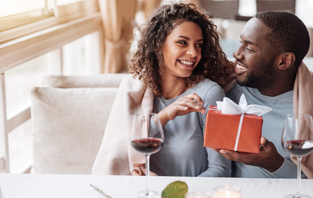 looking for love: For all my love to you. Loving smiling happy African American man sitting in the restaurant and looking at his girlfriend while being covered with the blanket and giving a present in the box to her Stock Photo