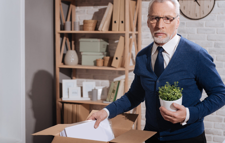 dismissed: Sad dismissed office worker putting away his things Stock Photo