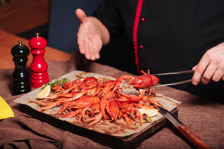 spicy food: Close up of mans hands demonstrating crayfishes in restaurant