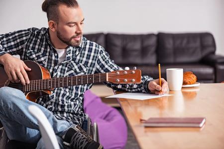 music lyrics: Talented handicapped guy writing letras de canciones Foto de archivo