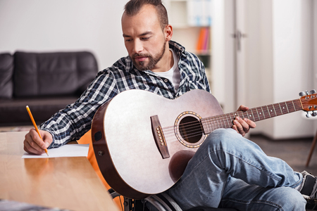 Handicapped musician writing down music chords