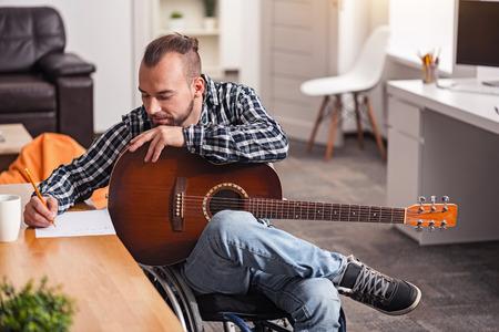 sit down: Hombre discapacitado enfocado en la composición de canciones Foto de archivo
