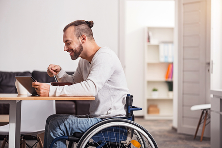 selfcare: Smiling disabled guy reading emails during breakfast Foto de archivo