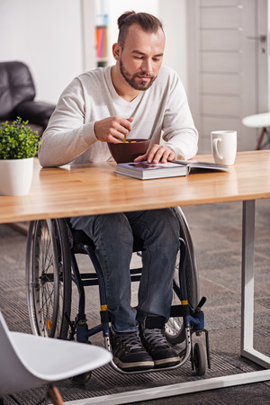 selfcare: Young disabled guy enjoying his morning meal