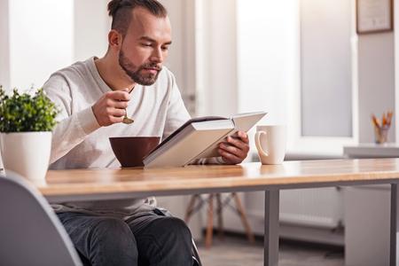 selfcare: Focused handicapped man having breakfast Foto de archivo