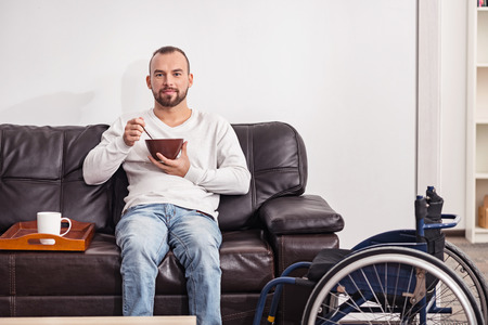 selfcare: Positive disabled man having cereal in the living room