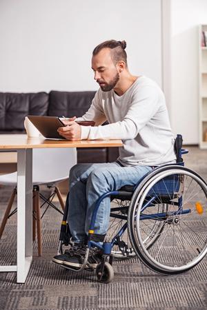 autocuidado: Focused handicapped man watching morning news Foto de archivo