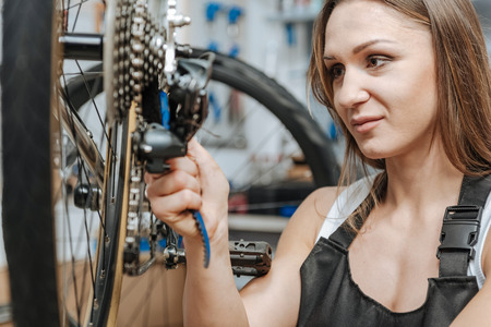 Cheerful craftswoman mending the chain of the bicycle Stock Photo