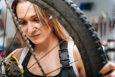 Charming young craftswoman wiping fuel oil in the workshop Stock Photo