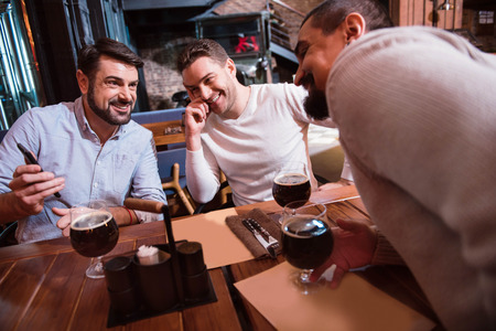 Cheerful positive men looking at the smartphone screen Stock Photo