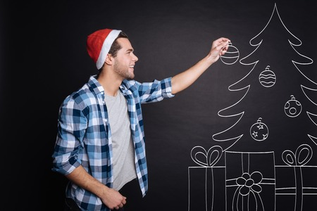 manhood: Positive young man decorating a Christmas tree.