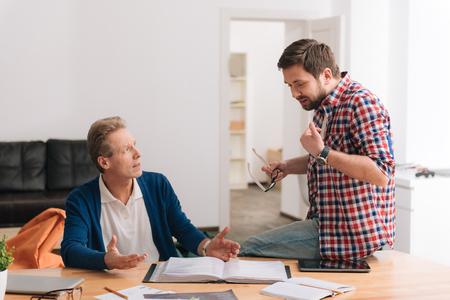 Nice bearded man explaining something to his colleague Stock Photo
