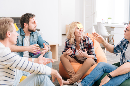 Joyful delighted group of office workers playing a game