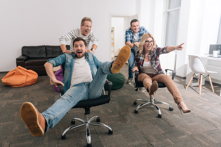 Positive cheerful men pushing office chairs