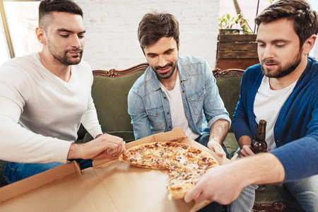 manhood: Attractive young men taking slices of pizza Stock Photo