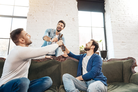 manhood: Joyful handsome men drinking beer