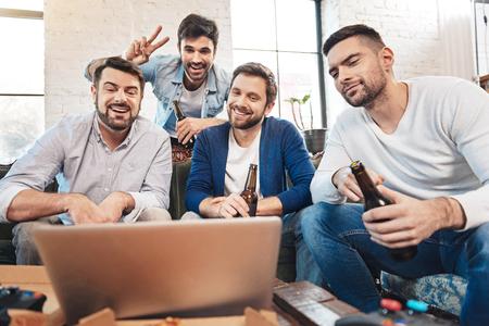 manhood: Cheerful positive friends speaking via the Internet Stock Photo