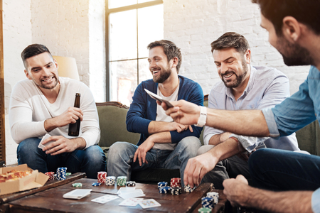 Cheerful pleasant men playing the poker game