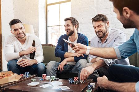 manhood: Cheerful pleasant men playing the poker game