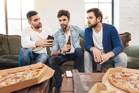 manhood: Handsome brunette man looking at the smartphone screen