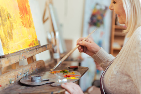 easel: Female artist painting a picture in class