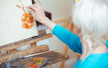 Female artist painting picture with putty knife.