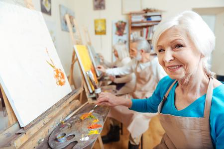 koncentrovaný: Žena umělec usmívající se v malířském studiu Reklamní fotografie