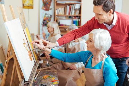 the elderly tutor: Delighted artist helping elderly woman in painting studio