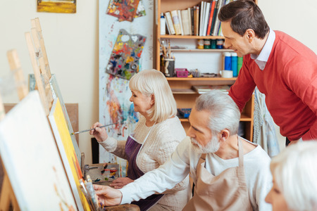 Handsome artist controlling his colleagues in painting class Stock Photo