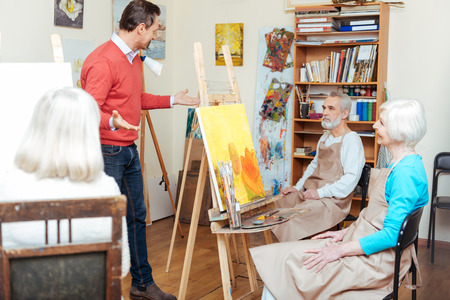 the elderly tutor: Handsome artist lecturing in painting school