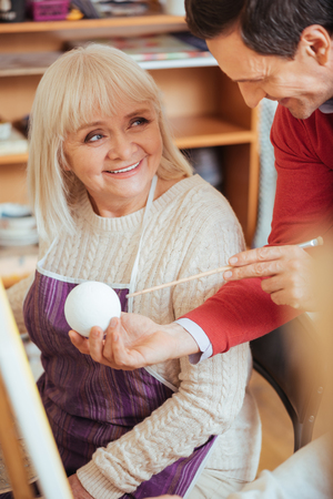 the elderly tutor: Smiling artist demonstrating a ball in painting studio
