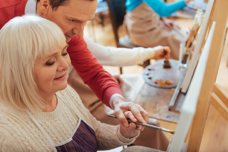 the elderly tutor: Concentrated man helping elderly woman in painting studio Stock Photo