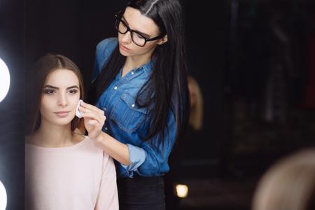Professional makeup artist using a cotton pad