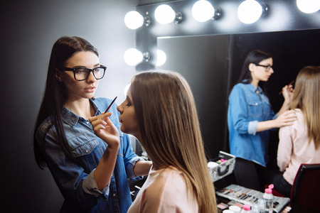 Nice attractive makeup artist using a cosmetic brush