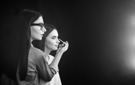 Nice serious makeup artist working with a model