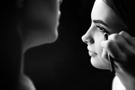Professional female visagiste using the eyeliner