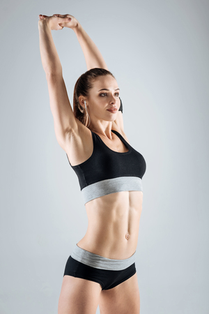 persistence: Motivated girl stretching on a grey background
